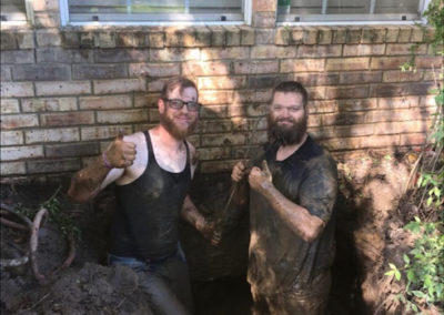 Two employees in the mud.